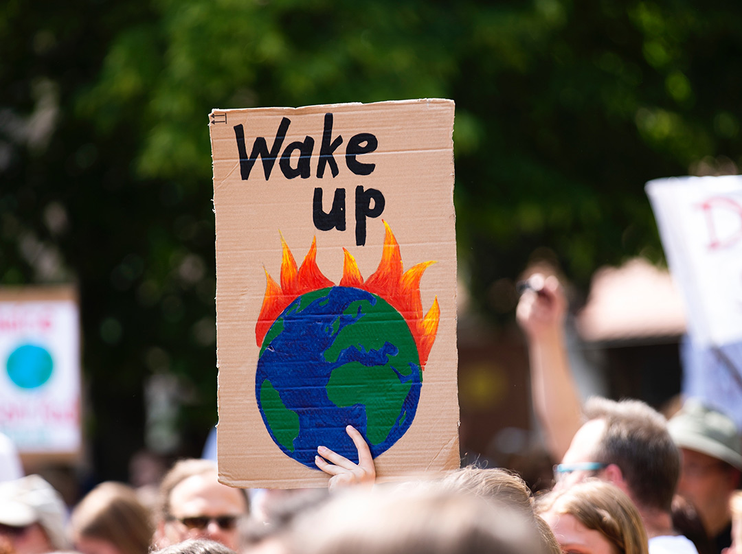 Protestors with home made banner showing the earth on fire with the words Wake Up